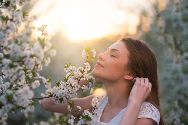 Una donna mentre sente il profumo dei fiori.