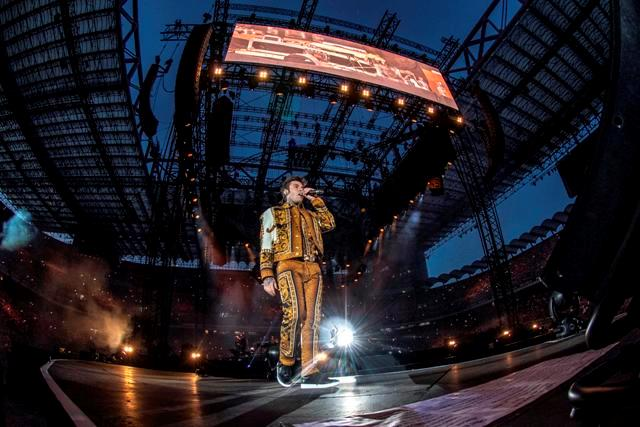 Fedez, in piedi, canta sul palco di San Siro
