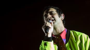 Cosmo, in piedi: primo piano mentre canta con il microfono in mano