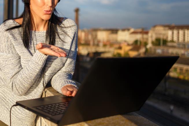 Una ragazza manda un bacio rivolta allo schermo di un computer
