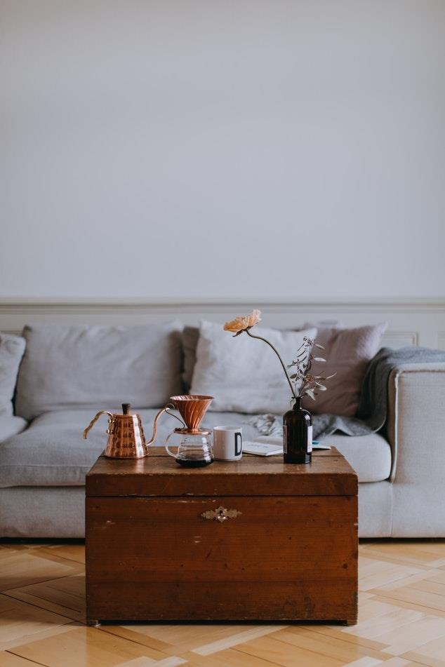 Salotto con divano grigio chiaro e baule vintage