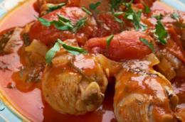 Primo piano di pezzi di pollo con pomodori pelati e prezzemolo tritato