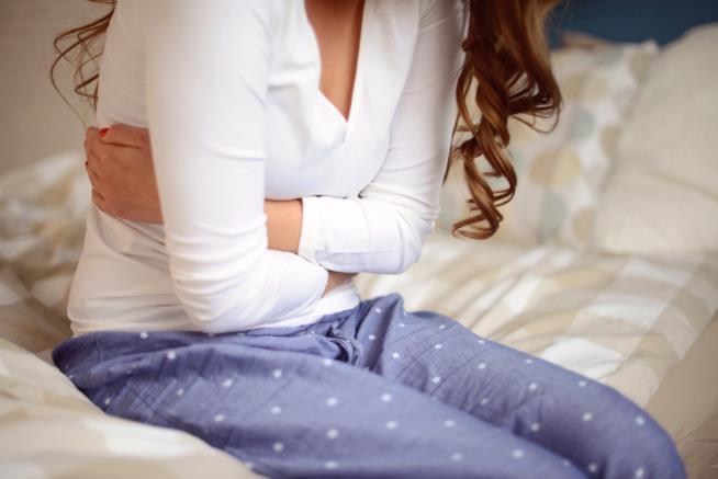 Una donna è seduta sul letto con le mani intorno al ventre