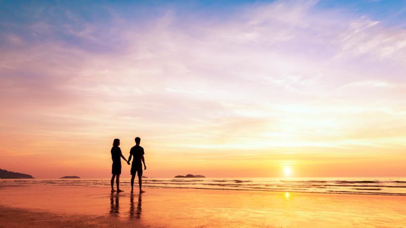 Coppia in spiaggia che guarda il tramonto