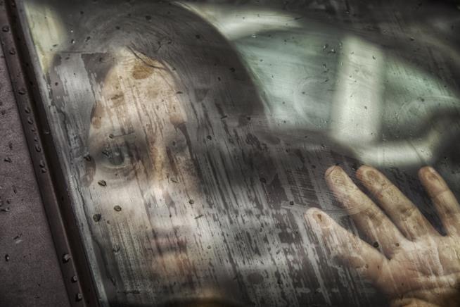 Volto di donna disperata oltre il finestrino di un'auto