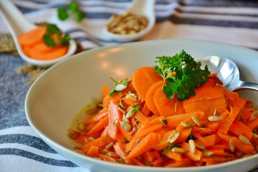 Piatto di ortaggi arancioni e semi di girasole