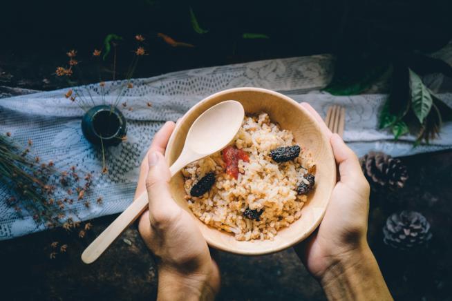 Mani di uomo con una ciotola di riso