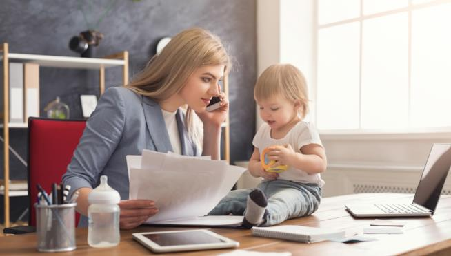 Una donna che lavora mentre guarda il figlio piccolo.