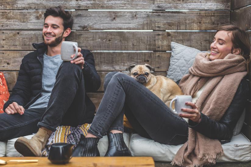 Coppia seduta in una baita con un cane
