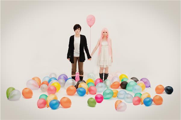 Una coppia asiatica si tiene per mano circondata da palloncini colorati