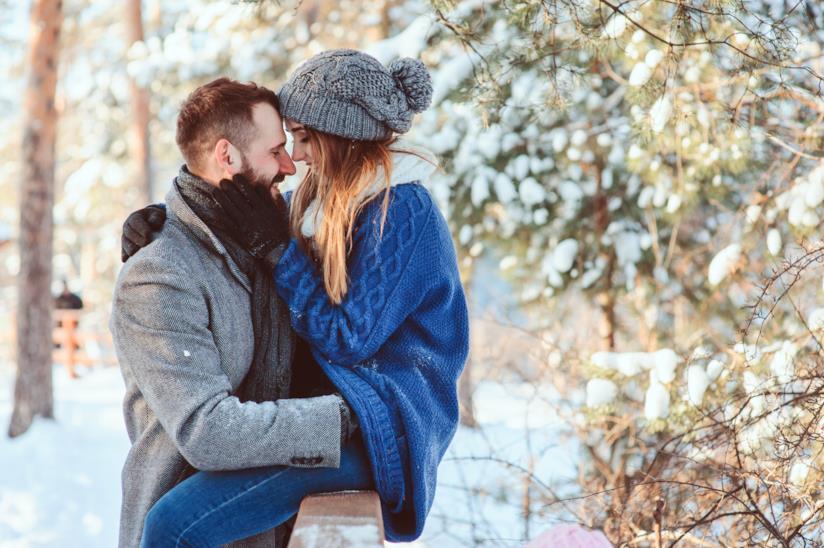 Una coppia si sta per baciare in un paesaggio innevato
