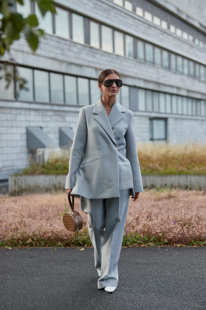 Completo giacca-pantalone abbinato a pumps bianche e borsa a mano