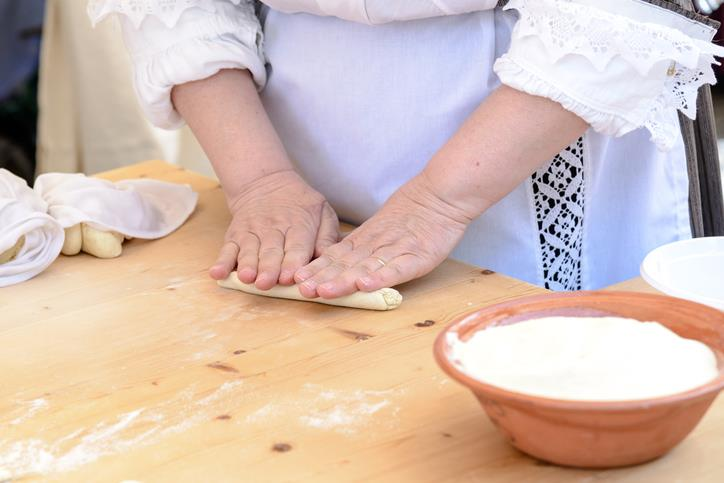 Una donna con costume tradizionale sardo cucina