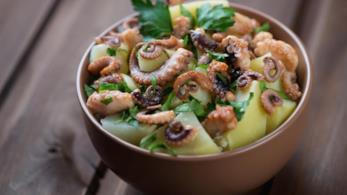 Ciotola marrone con all'interno polpo, patate, rucola e prezzemolo, poggiato su tavolo di legno