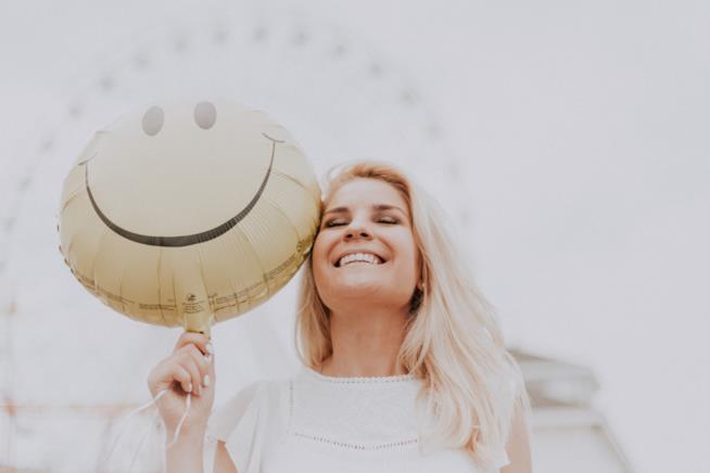 Ragazza sorride tenendo in mano un palloncino a forma di smile