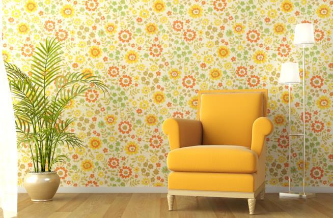 Parete del soggiorno rivestita con carta da parati a fantasia floreale in giallo e arancio