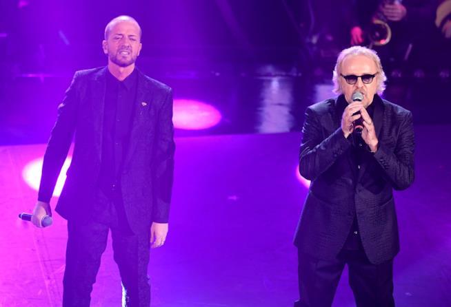 Raf e Umberto Tozzi, in nero, in piedi, cantano al microfono su sfondo viola