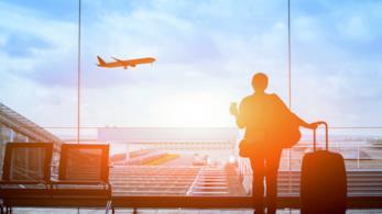 Una donna in aeroporto, con una valigia e un caffè in mano, guarda un aereo che decolla
