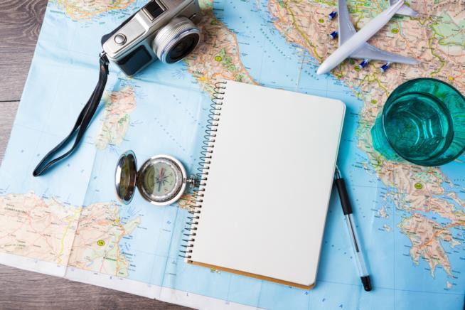 Una cartina geografica dove sopra sono posati diversi oggetti inerenti al tema viaggio