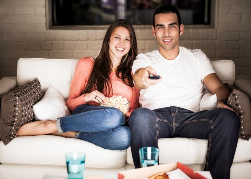 Una coppia è seduta sul divano a guardare la televisione