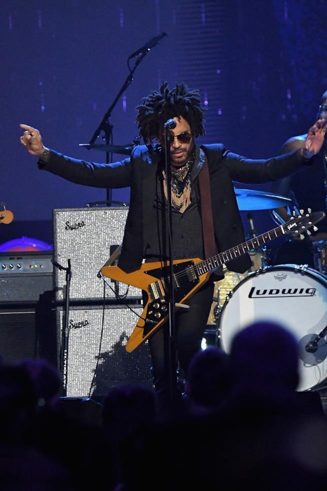 Lenny Kravitz, in nero, con la chitarra al collo, di fronte a degli amplificatori e al microfono
