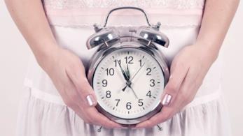 Donna regge una sveglia con entrambe le mani