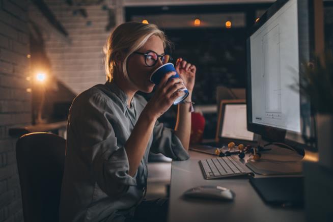 Una donna di fronte al computer di sera