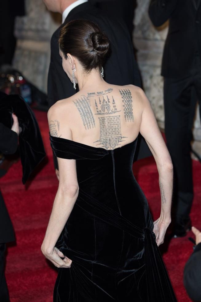 Angelina Jolie di spalle, con la schiena ricoperta di tatuaggi