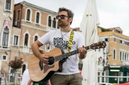 Jack Anselmi con una maglietta bianca, mentre suona la chitarra, con lo sfondo di Venezia