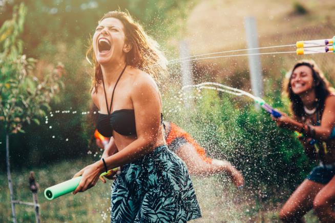 Due ragazze giocano allegre con la pistola ad acqua