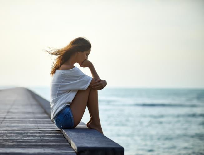 Una ragazza siede da sola pensierosa su un molo