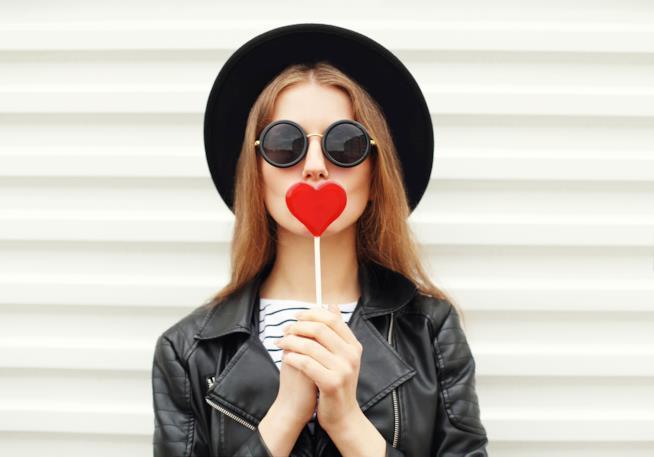 Una donna scherzosa con lecca lecca a cuore