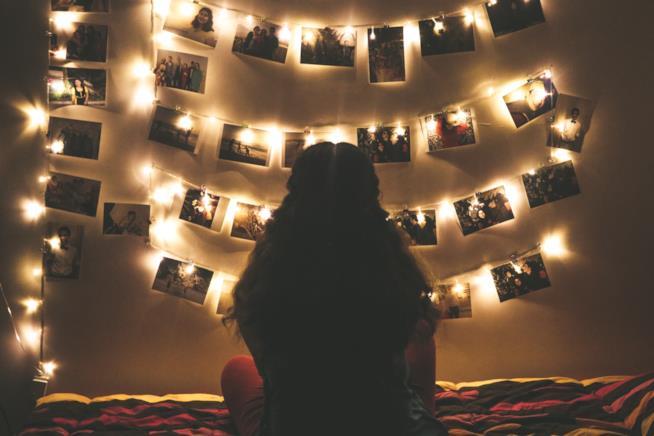 Ragazza da sola seduta sul letto guarda delle fotografie appese al muro