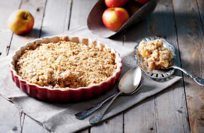 Crumble di mele su tavolo di legno circondato da mele e cucchiai