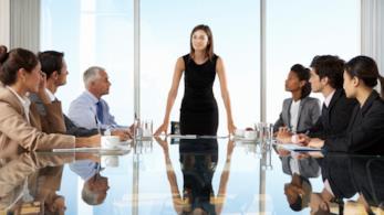 Una donna manager tiene capo ad una riunione in piedi davanti ai colleghi intorno ad un tavolo
