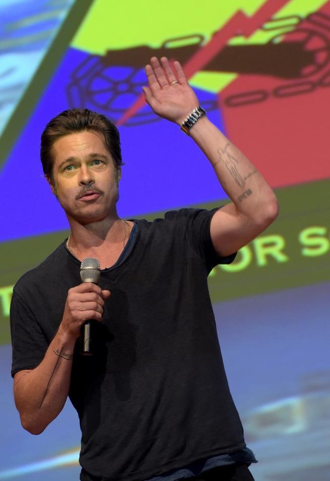 Brad Pitt parla al microfono con il braccio sinistro alzato