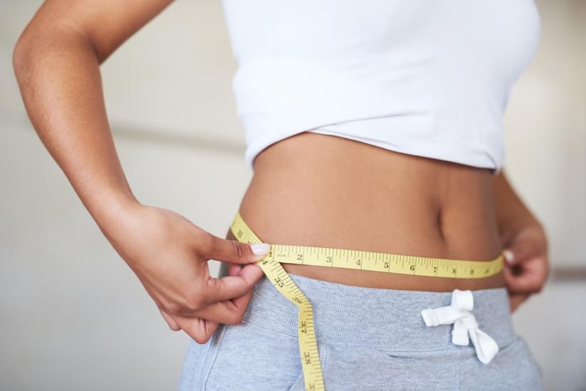 Una ragazza si misura il girovita con un centimetro
