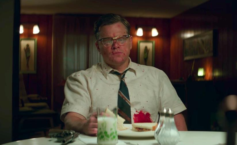 Matt Damon ricoperto di sangue mangia un tramezzino in una scena di Suburbicon