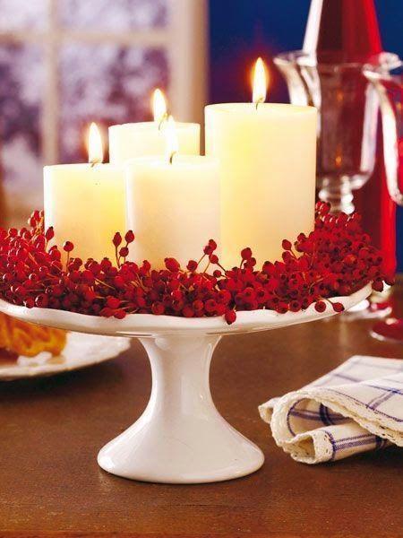 Centrotavola con candele bianche e bacche rosse