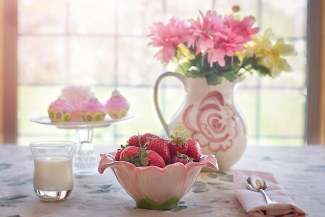 Una tavola apparecchiata con fiori e alimenti.