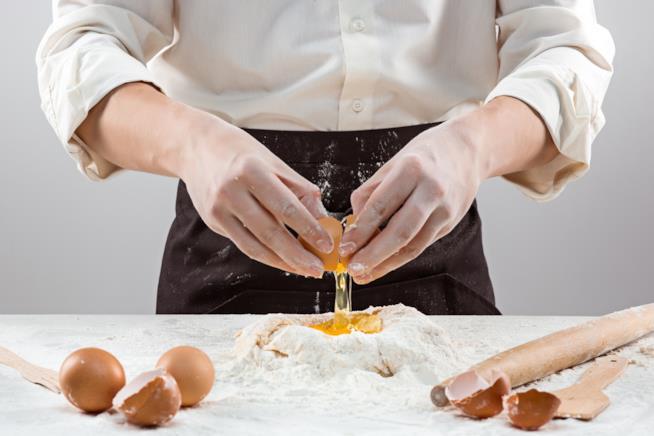 Uova aggiunge alla farina disposta a fontana su un tavolo