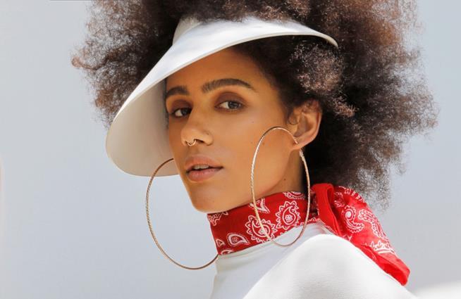 Nathalie Emmanuel in primo piano con orecchini a cerchio e foulard rosso