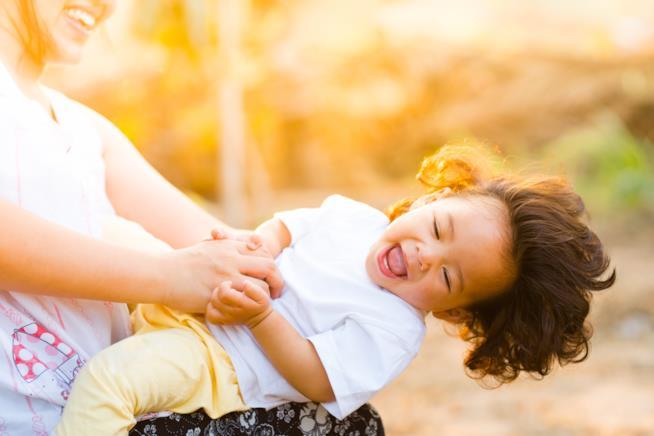 Bambino ride allegro giocando con la madre