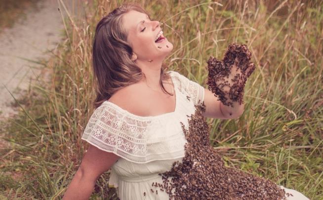 una donna col pancione coperta di api