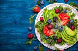 piatto colorato con insalata, avocado, frutti di bosco appoggiato su un piano azzurro