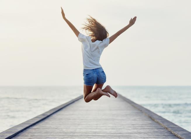 Ragazza su un molo che salta per la felicità