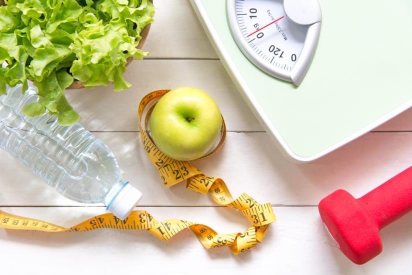 Tavolo con sopra bilancia, peso, acqua e mela