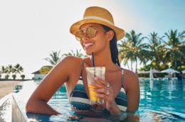 Ragazza in piscina che beve un drink rinfrescante