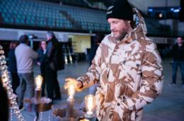Jovanotti, con una giacca mimetica, tocca una lampadina di un lampadario