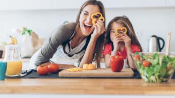 Mamma e figlia in cucina che giocano con le verdure tagliate